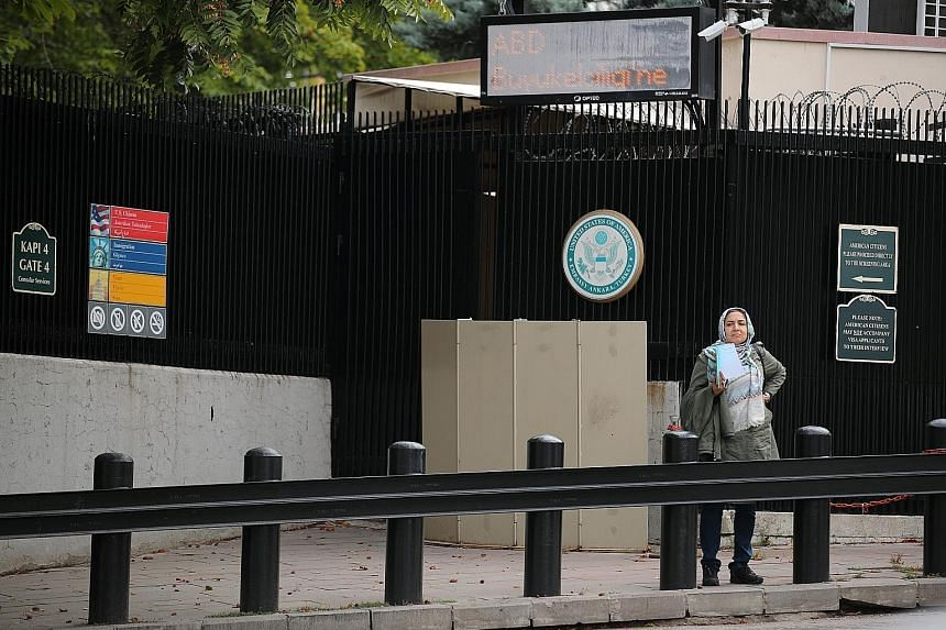 A woman waiting in front of the visa application office entrance of the United States Embassy in Ankara yesterday. The US has stopped visa services at all its missions in Turkey. Ankara yesterday summoned the US Embassy's deputy chief of mission, Mr