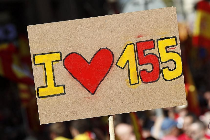 A placard - supporting Article 155 of the Spanish Constitution, which allows direct rule from Madrid and cancels the authority of autonomous regions - at a Barcelona rally championing the unity of Spain on Sunday.