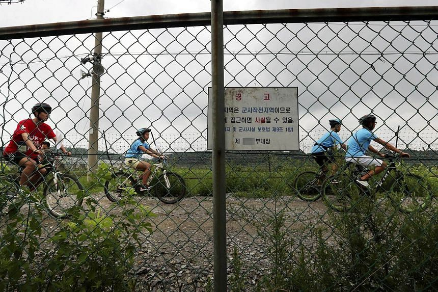 People ride bicycles on a road that runs along the Demilitarized Zone separating the two Koreas near the Imjingak Pavilion in Paju, north of Seoul, South Korea, on July 17, 2017.