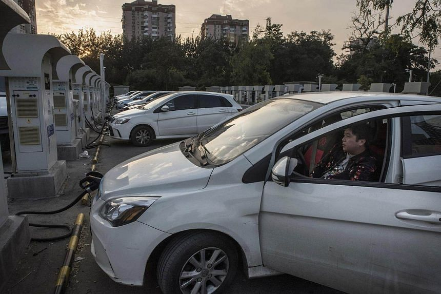 A driver waits for his car to be charged at a station for electric vehicles in Beijing, on Oct 5, 2017. China has become the world's biggest supporter of electric cars.