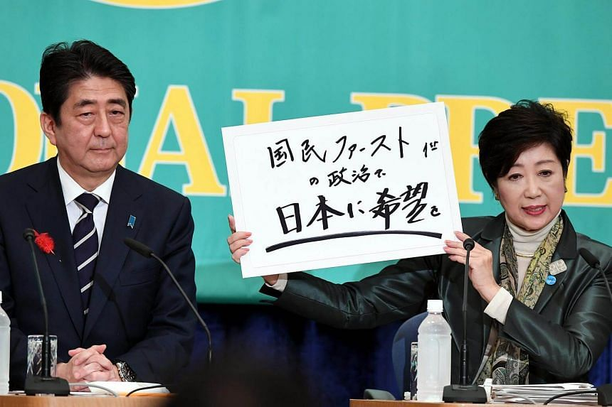 Japanese PM Shinzo Abe (left) sits next to the Head of Japan's Party of Hope and Tokyo Governor Yuriko Koike at a Japanese parties leaders' debate, on Oct 8, 2017.