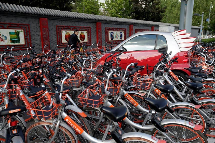 Mobike's shared bicycles are parked around a car in Beijing, China. The capital's transportation management authority prohibited an increase of shared bikes on its roads in September.