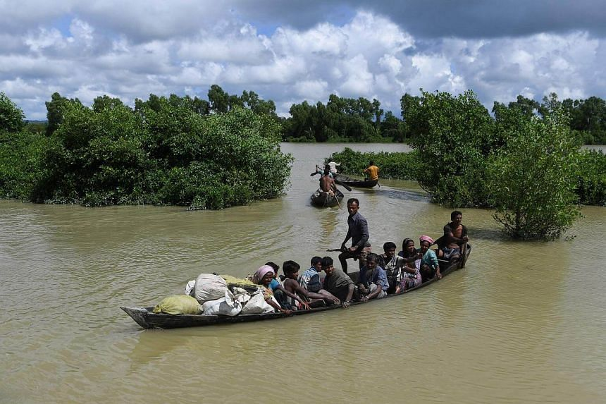 Rohingya refugees arrive on a boat after crossing the Naf river from Myanmar into Bangladesh in Whaikhyang on Oct 9, 2017.