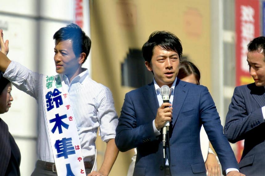 Mr Shinjiro Koizumi (right) of the ruling Liberal Democratic Party (LDP) stumps for party candidate Hayato Suzuki, 40, an incumbent one-term Lower House lawmaker, at a busy traffic intersection in Ikebukuro on on Oct 10.