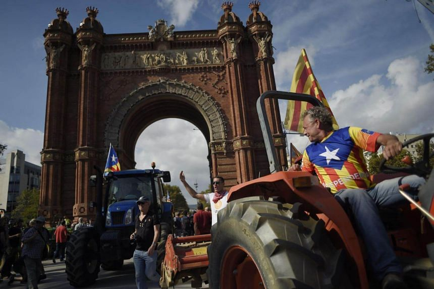 Supporters of Catalan independence drive with tractors through the Arc de Triomf in Barcelona on Oct 10, 2017.
