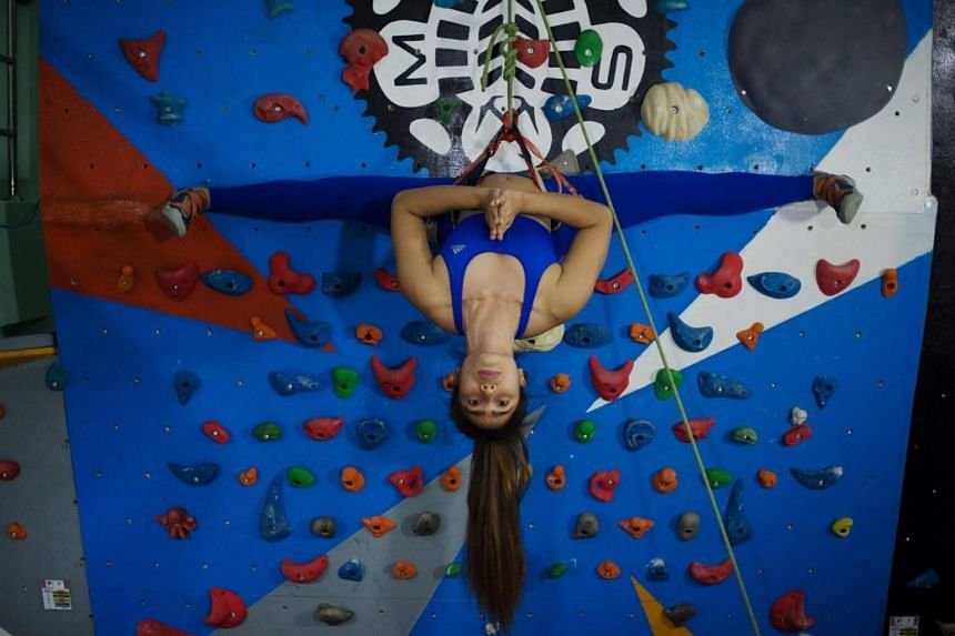Khin Myat Thu Zar, who teaches yoga professionally, performs a pose on a climbing wall during a class at a studio in Yangon.