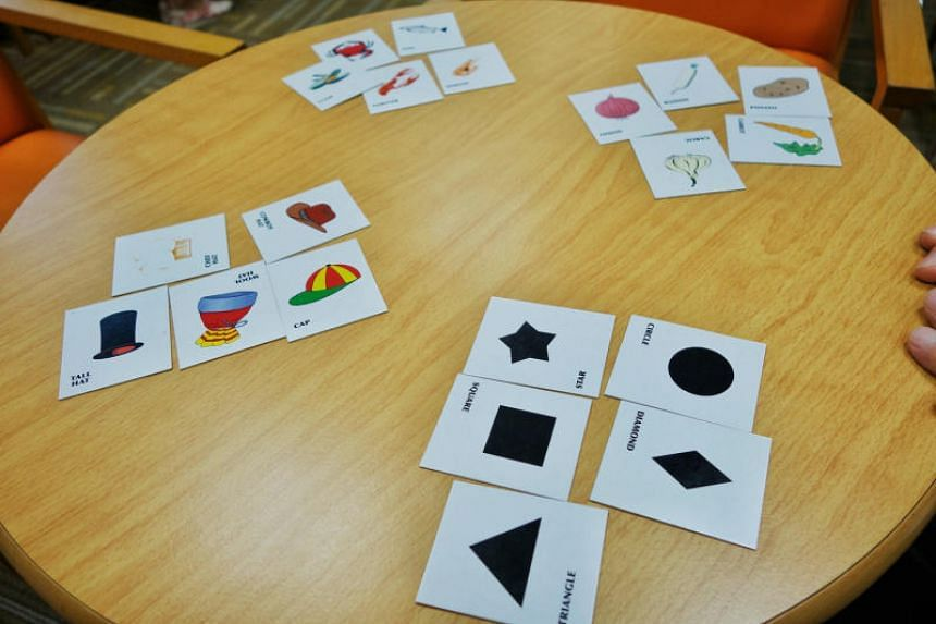 Elderly playing the game See Me, which trains one's memory and teaches memory strategies to those with mild dementia. The game requires them to remember the pictures on the cards through categorisation and association.