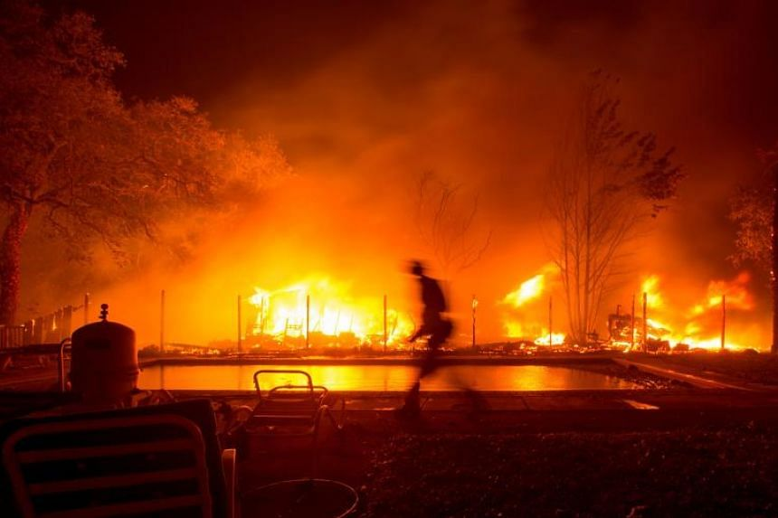 A firefighter walks near a pool as a neighbouring home burns in the Napa wine region in California on Oct 9, 2017, as multiple wind-driven fires continue to whip through the region.