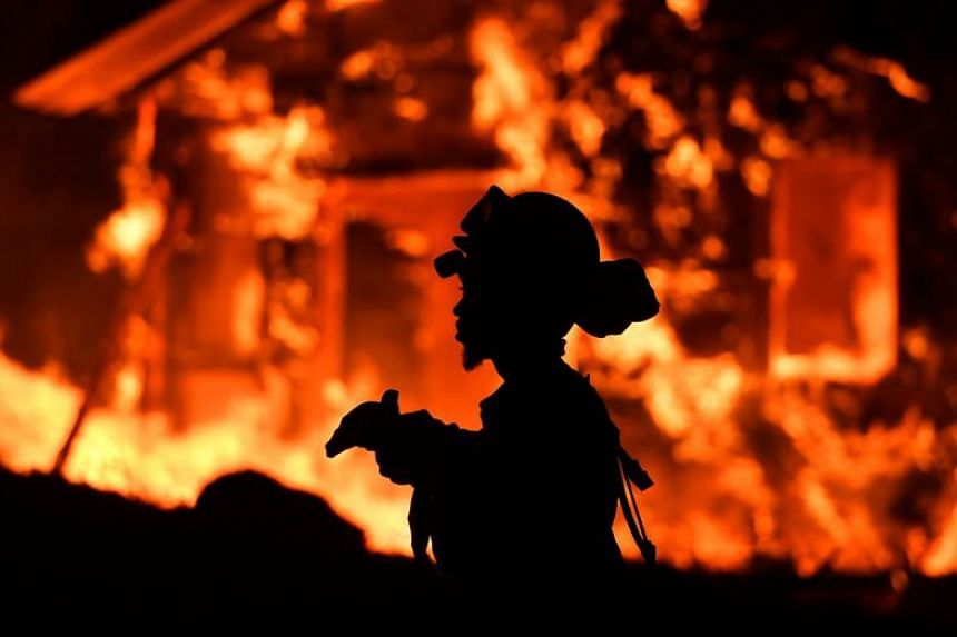 An inmate firefighter monitors flames as a house burns in the Napa wine region in California on Oct 9, 2017, as multiple wind-driven fires continue to whip through the region.