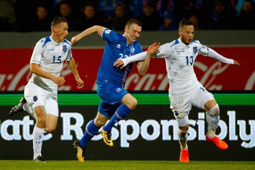 (From left) Kosovo's Mergim Vojvoda, Iceland's Jon Dadi Bodvarsson and Kosovo's Amir Rrahmani fight for the ball during the Fifa World Cup 2018 qualification match between Iceland and Kosovo in Reykjavik, Iceland, on Oct 9, 2018.