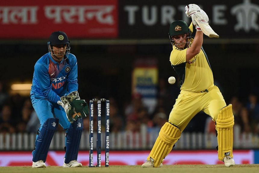 Australia's Aaron Finch (right) plays a shot as Indian wicket keeper Mahendra Singh Dhoni looks on during the first T20 match between India and Australian at the JSCA international stadium in Ranchi, on Oct 7, 2017.