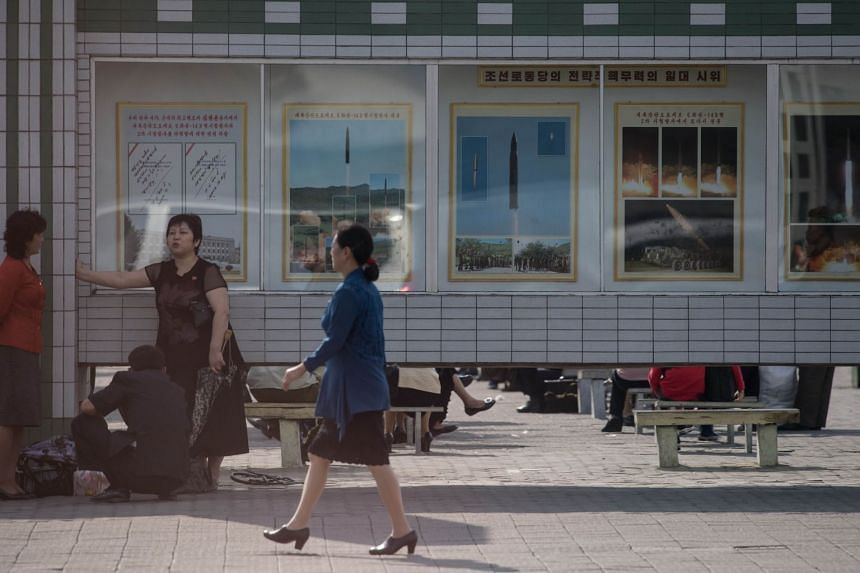 Women chatting near posters displaying images of North Korean missile test launches, in Pyongyang, on Sept 22, 2017.