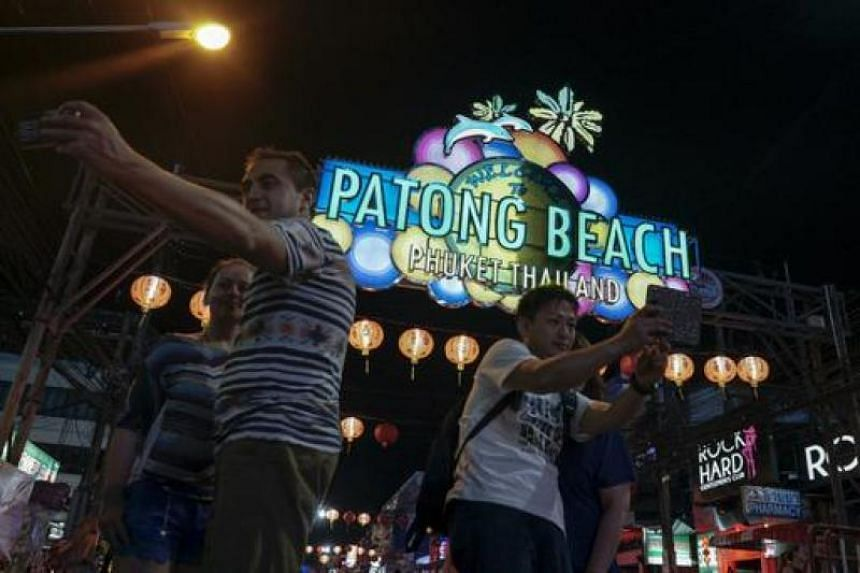 Tourists take selfie on a street near Patong beach in Phuket on March 19, 2016.