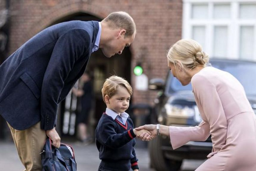 Britain's Prince George (centre), accompanied by his father Prince William (left), arrives for his first day at Thomas's school where he was met by Helen Haslem (right), head of the lower school in Sept, 2017.