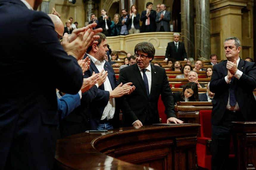 Catalan President Carles Puigdemont (centre) is applauded after delivering his speech