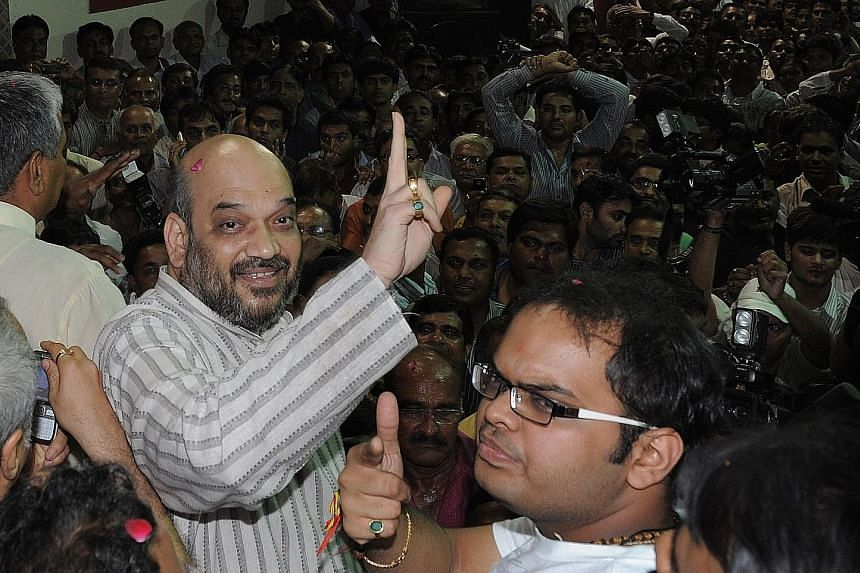 Mr Amit Shah (with raised finger) and his son Jay (in spectacles) in October 2010. Mr Jay Shah is suing The Wire for its report into his commodity trading business. The report said the turnover in Mr Jay Shah's firm grew by 16,000 times after 2014, w