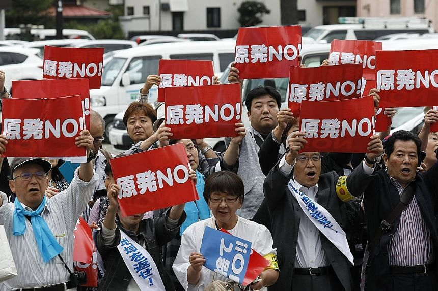 """Plaintiffs hold up banners reading """"No Nuclear Power Plant"""", before winning their class action suit at the Fukushima district court yesterday."""
