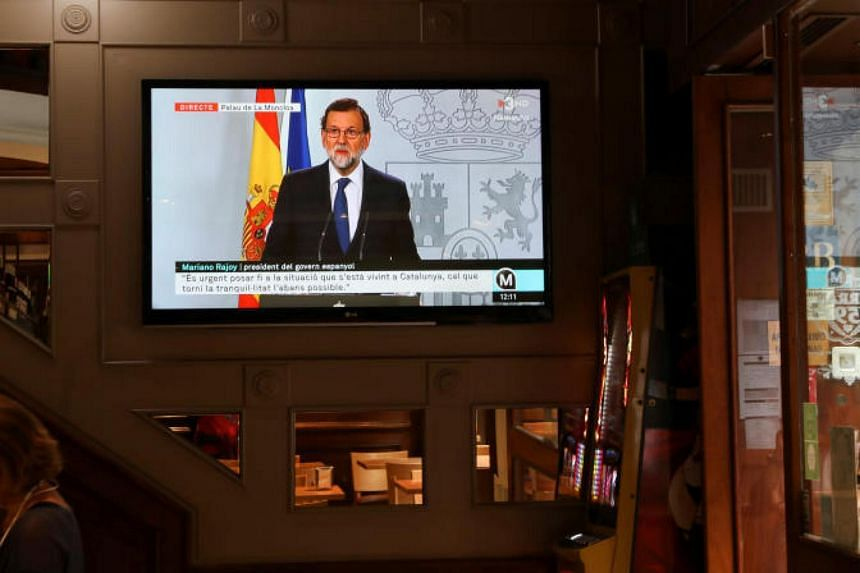Spain's Prime Minister Mariano Rajoy is seen delivering a statement on a television screen at a bar in Barcelona, Spain on Oct 11, 2017.