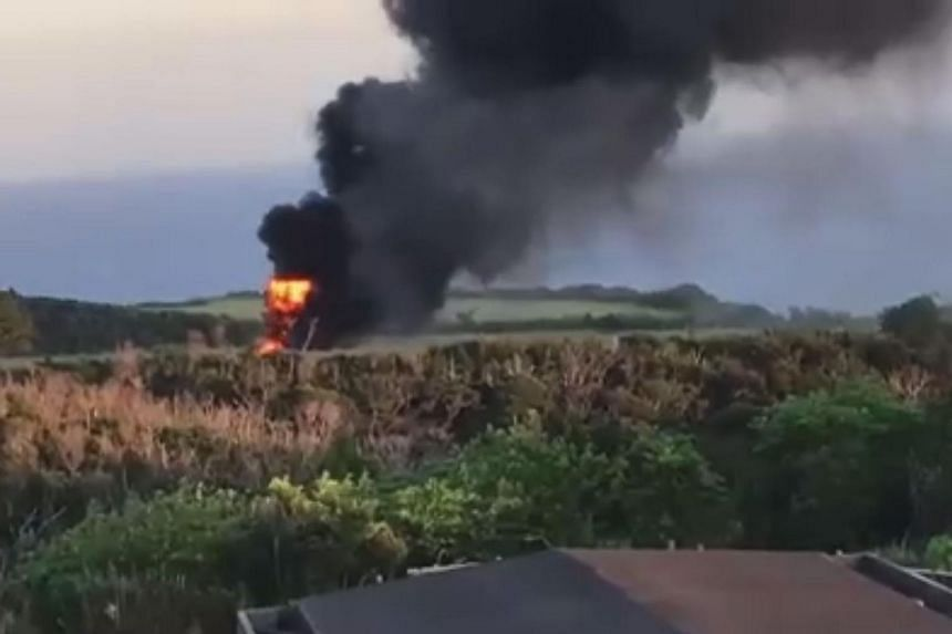 Smoke and flames are seen rising from the crash site of a US Marine Corps CH-53 helicopter in Okinawa, in this screengrab from a handout video given to the Yomiuri Shimbun, on Oct 11, 2017.