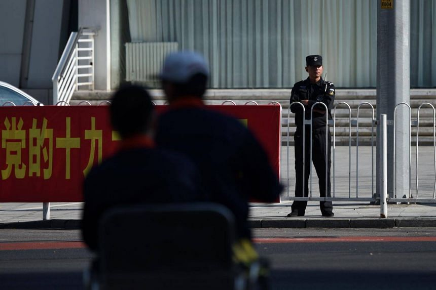 A security guard stands behind a China's 19th Party Congress promotion billboard in Beijing on Oct 11, 2017.
