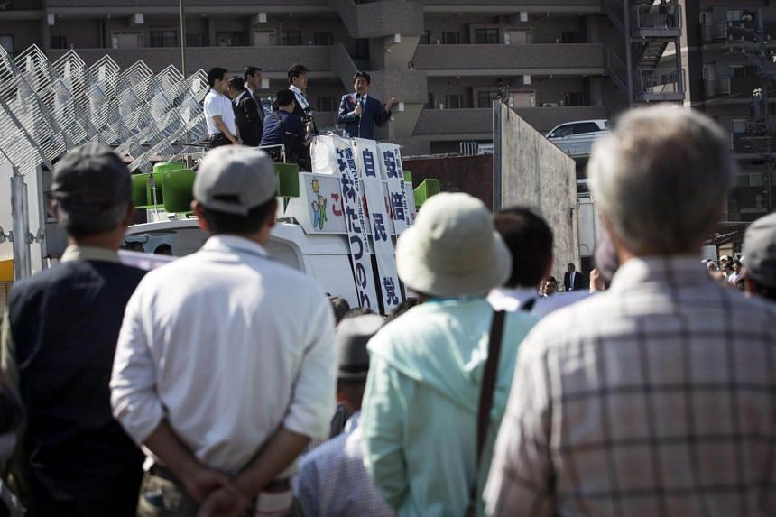 Japanese Liberal Democratic Party supporters listen to Prime Minister Shinzo Abe (centre) during an election campaign in Yaizu, Shizuoka prefecture, on Oct 11, 2017.
