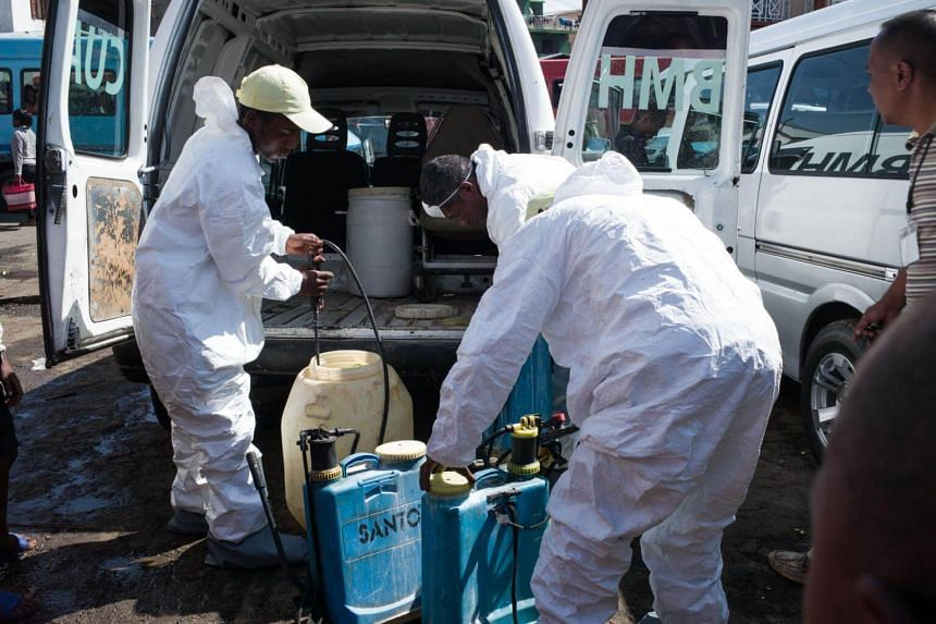 Council workers prepare to spray disinfectant during the clean-up of the market of Anosibe in the Anosibe district on Oct 10, 2017.