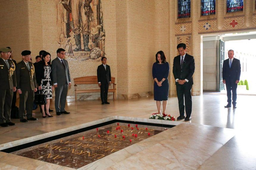 Mr Ong and his wife, Mrs Diana Ong, observing a moment of silence after laying a wreath at the Australian War Memorial.