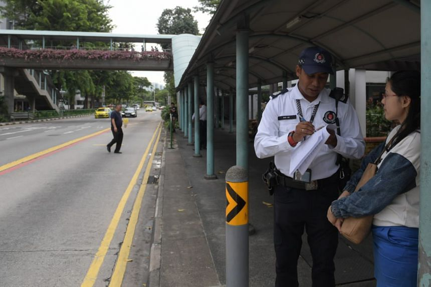 A jaywalker along North Bridge Road being warned by a traffic police officer.