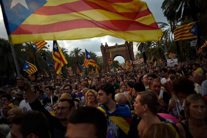 Supporters of an independence for Catalonia listen to Catalan president Carles Puigdemont's speech broadcasted on a television screen at the Arc de Triomf.