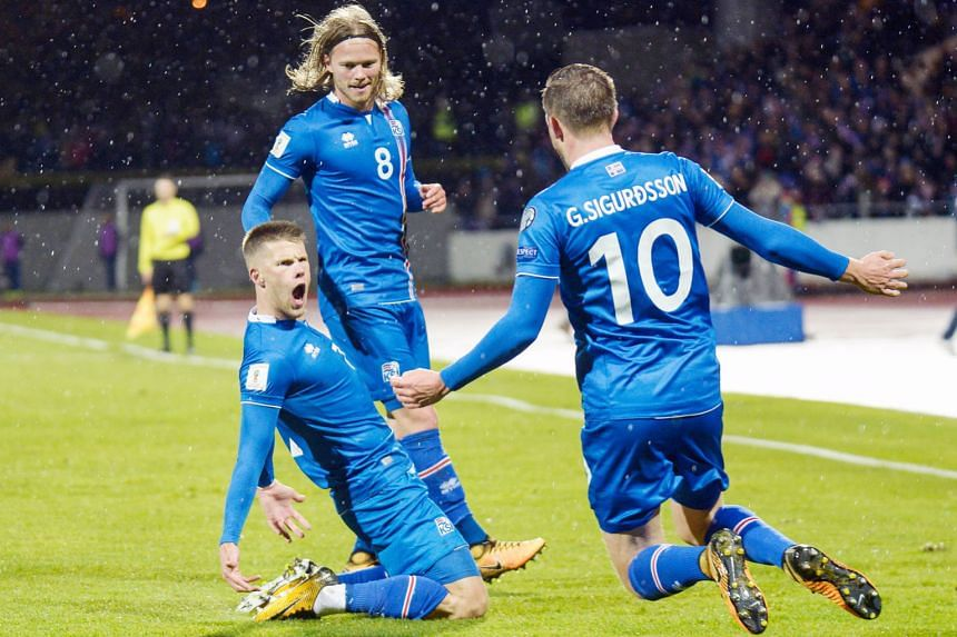 Iceland players celebrate after becoming the smallest nation to progress to a World Cup Finals, beating Kosovo 2-0 on Monday in Reykjavik. Johann Berg Gudmundsson, on his knees after scoring, is joined in his moment of glory by Birkir Bjarnason and G