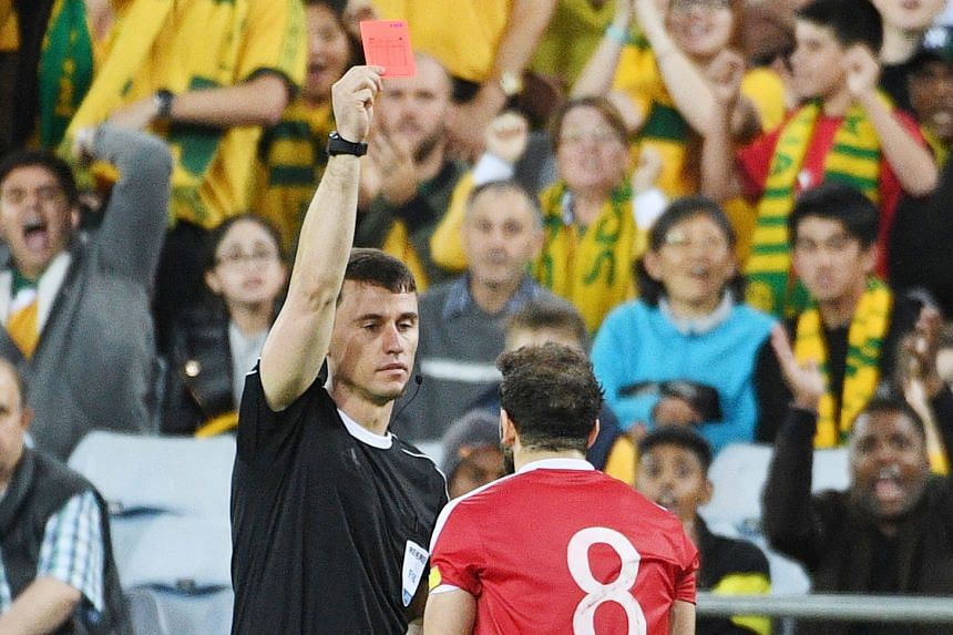Referee Ravshan Irmatov sending Syria's Mahmoud Al-Mawas off in the first half of extra time.