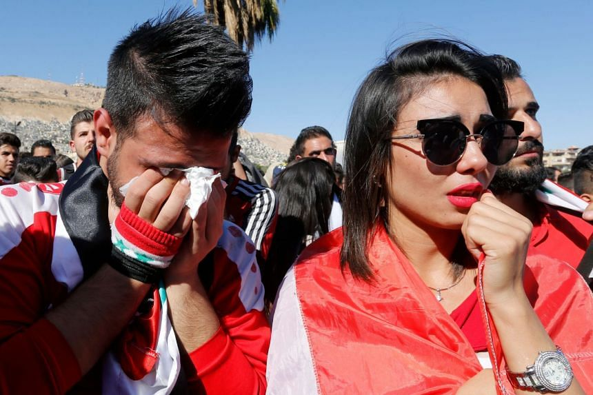 Syrians react after their national team lost to Australia in the World Cup qualifying play-off.