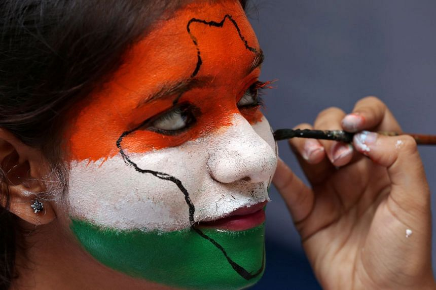 A girl gets her face painted in the colours of India's national flag, for Independence Day celebrations.