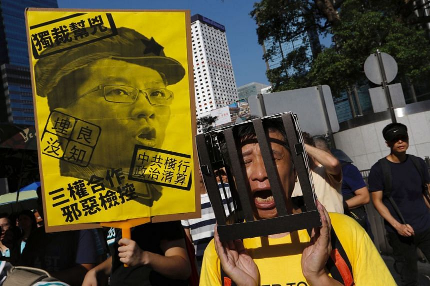 People protest the jailing of pro-democracy student leaders Joshua Wong, Nathan Law and Alex Chow, in Hong Kong, Aug 20, 2017.