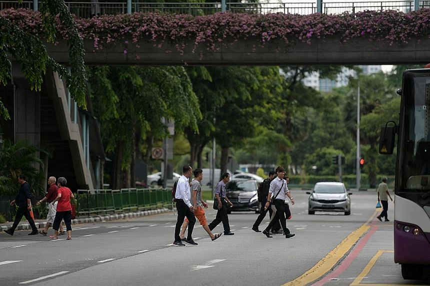 People jaywalking in North Bridge Road yesterday, despite having an overhead bridge and pedestrian crossing nearby. There were 161 accidents in which pedestrians jaywalked in the first six months of this year, up from 133 in the same period last year