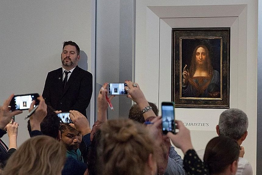 Leonardo da Vinci's Christ As Salvator Mundi (left) on display at Christie's in New York and Andy Warhol's Sixty Last Suppers (below).