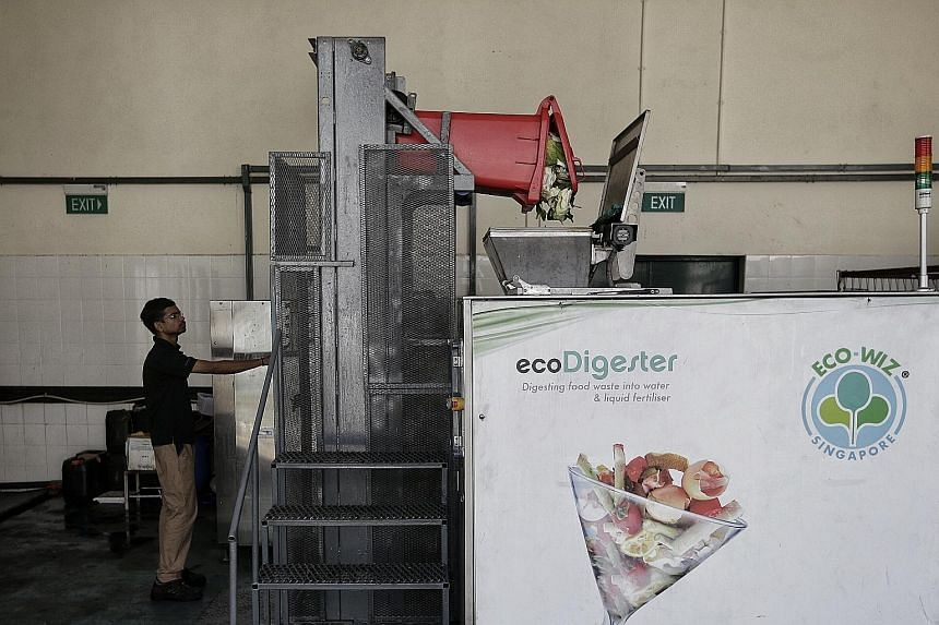 """Bins for food waste at the market and food centre at Block 628 in Ang Mo Kio Avenue 4. The pilot of a food digester here has """"performed according to expectations"""", said the National Environment Agency. The food digester in operation at Block 628 in A"""