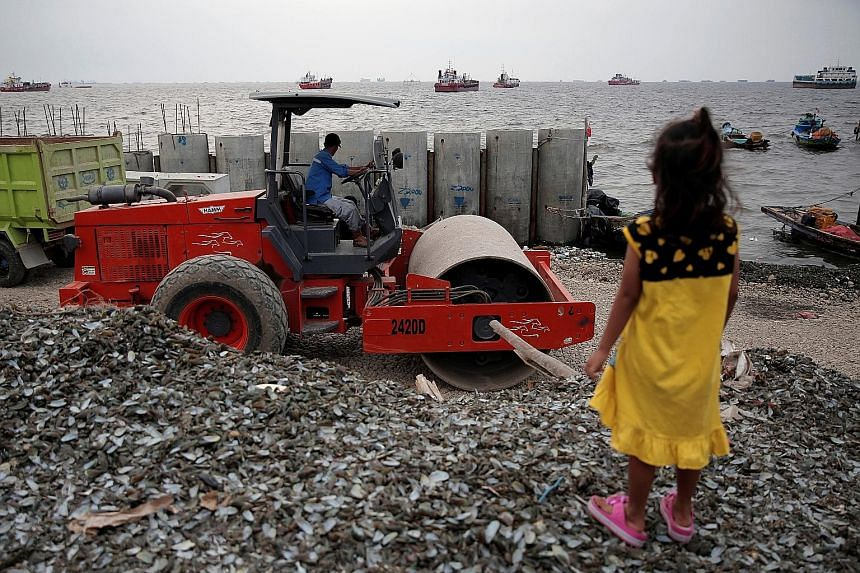 A child watching a worker operating heavy machinery for the construction of a concrete sea wall in North Jakarta in August. The low-lying Indonesian capital faces growing risks from rising sea levels, subsidence and annual flooding from more than a d