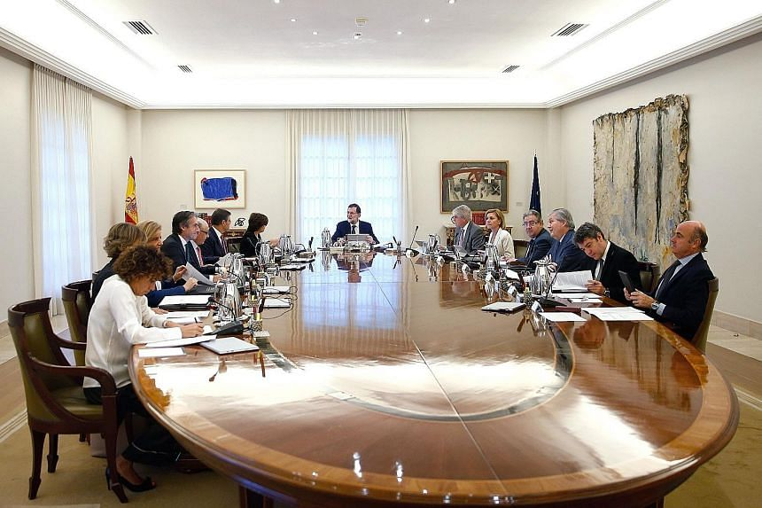 "Spanish Prime Minister Mariano Rajoy (centre) presiding over a crisis Cabinet meeting yesterday as the government vowed to examine ""all options"", hours after Catalonia's leaders said they had a mandate to declare independence but put it on hold."
