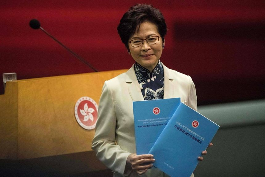 Hong Kong's Chief Executive Carrie Lam poses with copies of her first policy address as she arrives for a press conference at the Legislative Council in Hong Kong, on Oct 11, 2017.