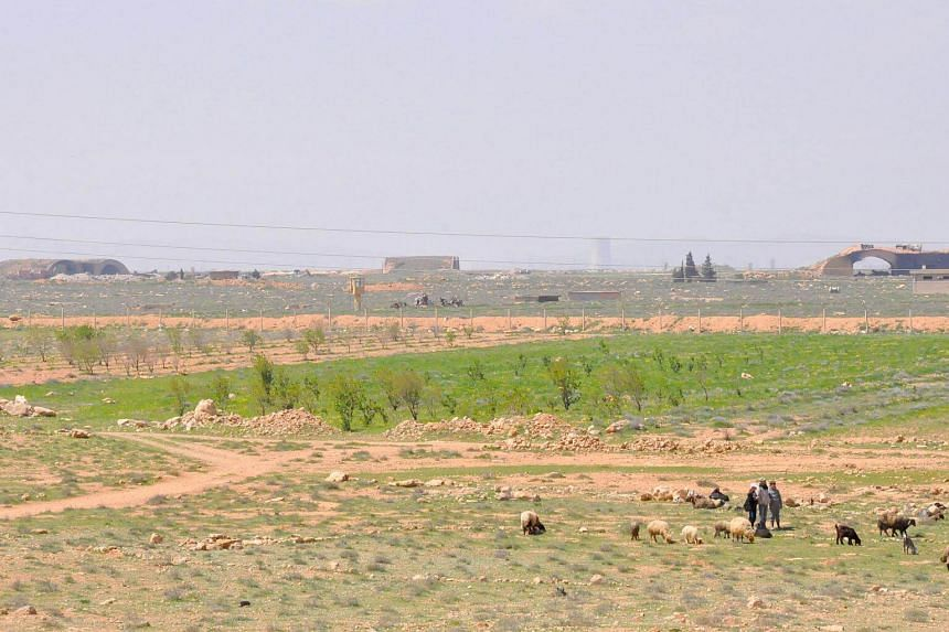 """Syrian shepherds tend their flock near the damaged Shayrat (""""ash-Shairat"""") airfield at the Syrian government forces military base targeted by US Tomahawk cruise missiles, southeast of the central and third largest Syrian city of Homs, on April 7, 201"""