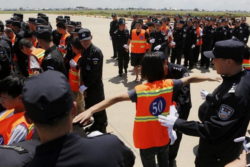 A Chinese suspect is checked by Cambodian and Chinese police officers at the Phnom Penh International Airport, in Phnom Penh, Cambodia, on Oct 12, 2017.