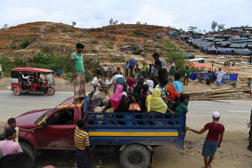 Rohingya refugees board a truck to move on to another camp at the Palangkhali refugee camp in Ukhia district on Oct 12, 2017.