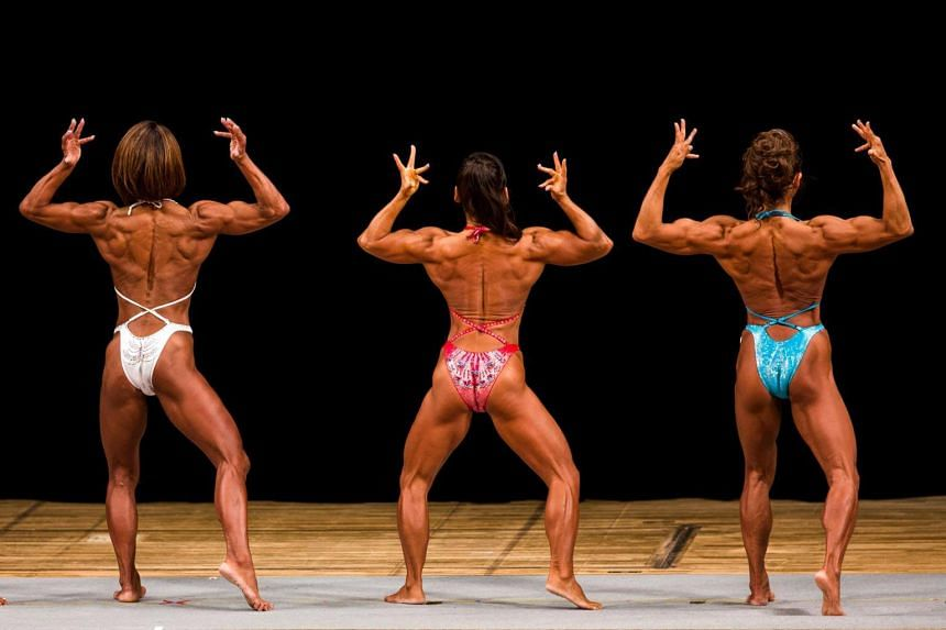 Japanese bodybuilders Megumi Sawada (left), Naoko Osawa (centre) and Eriko Shimizu pose during the Japan bodybuilding championships in Tokyo on Oct 9, 2017.