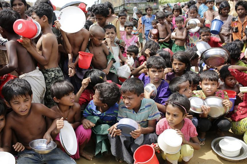 Rohingya children waiting outside a food centre to collect lunch at a camp in Palonkhali, Cox's Bazar, Bangladesh, on Oct 11, 2017.