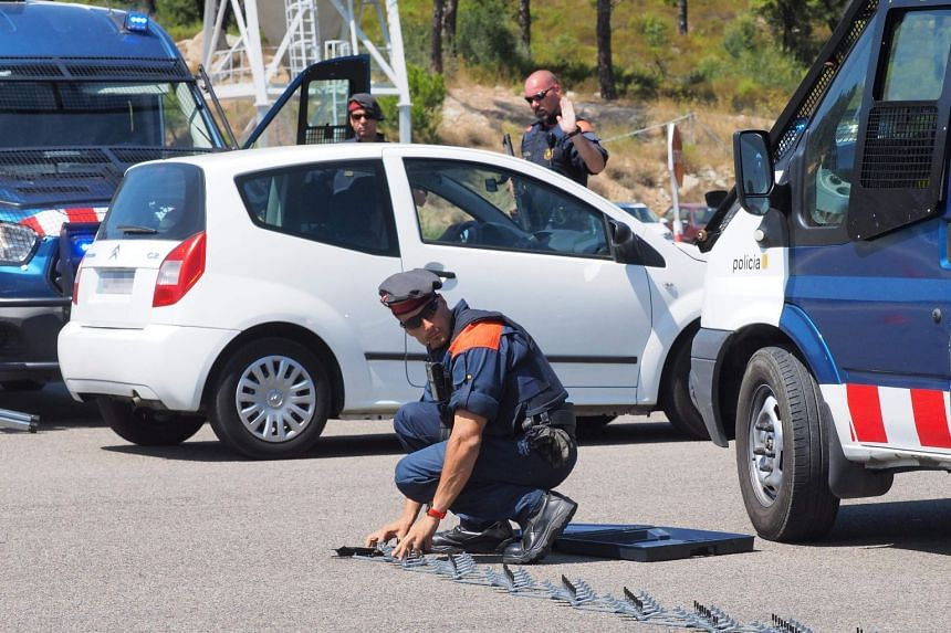 """A Spanish police officers deploys a """"spike- strip"""" as he controls vehicles on the Spanish-French border in August 2017."""