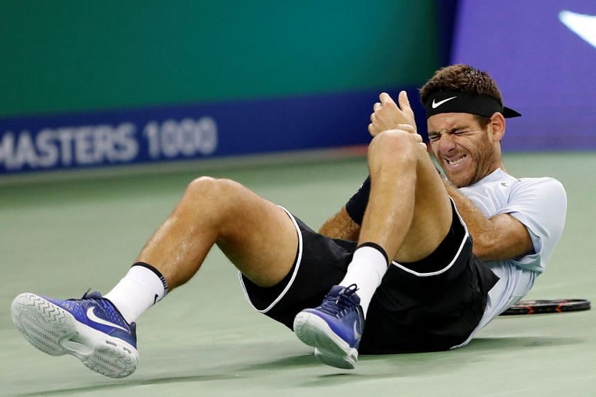 Del Potro holds his wrist after falling during the match.
