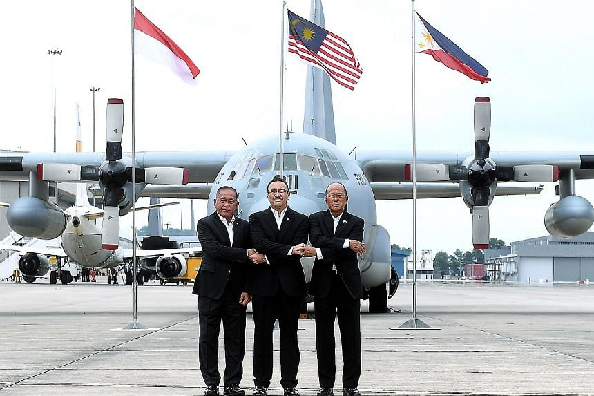 Malaysian Defence Minister Hishammuddin Hussein (centre) with his Indonesian counterpart Ryamizard Ryacudu (far left) and Philippine counterpart Delfin Lorenzana at the launch of the trilateral air patrols over the Sulu Sea yesterday in Subang, Selan