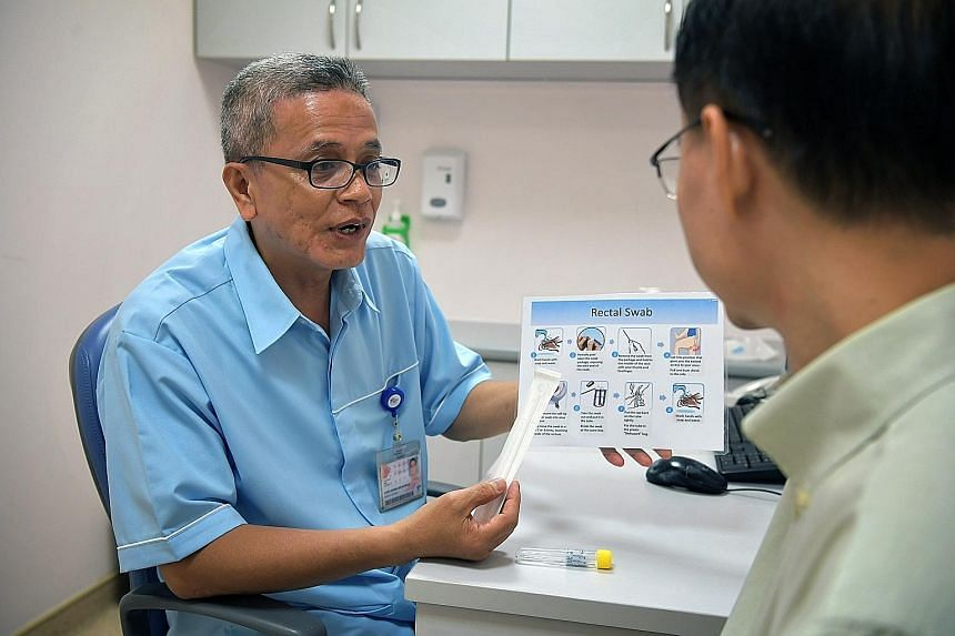 Nurse clinician Mohd Adnan Mahmud explaining to a patient how to use the new rectal swab kit.