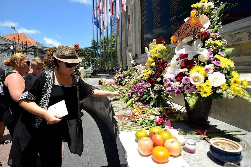 Foreign tourists paying their respects yesterday at the memorial for victims of the 2002 Bali bombings in the Kuta tourist district near Denpasar, on the Indonesian resort island of Bali, which marked the 15th anniversary of the blasts. The 2002 bomb